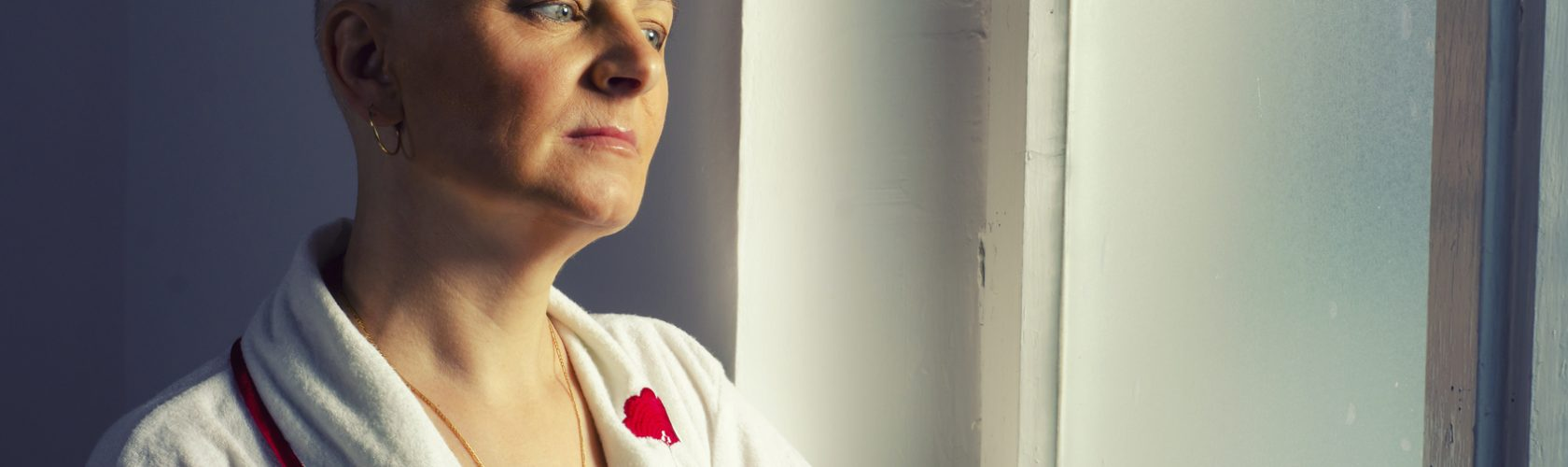 Bald woman suffering from cancer looking throught the hospital window.